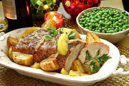 Deliciosa receta navideña para hacer lomo de cerdo con manzana papas al horno y chícharos verdes.